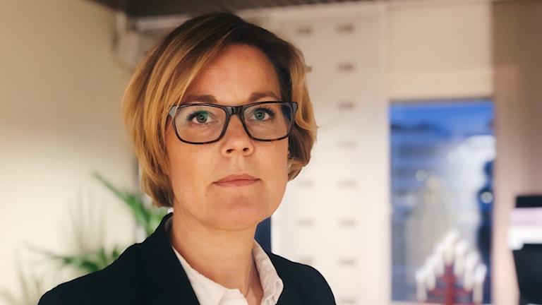 Porträtt av åklagare Carin Pedersen. Hon har kortklippt ljust hår och glasögon med svarta bågar. vit skjorta och svart kavaj.