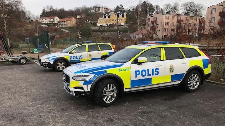Två polisbilar på parkeringsplats.