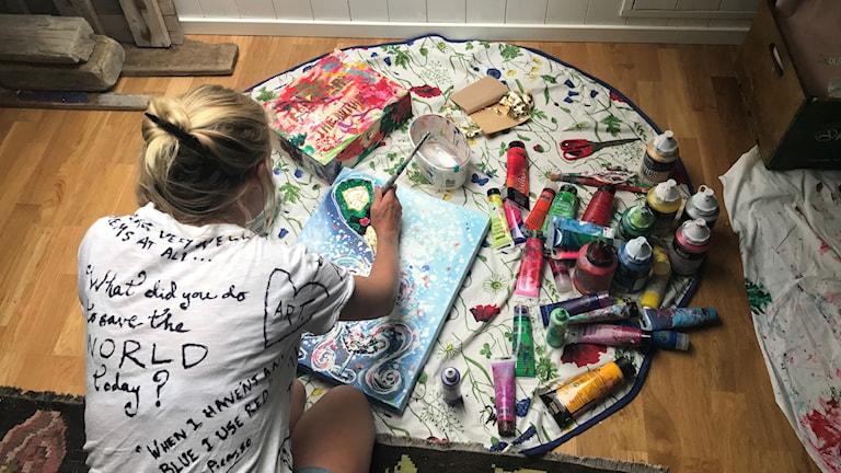 Charlotte Olsson sitter på golvet och målar