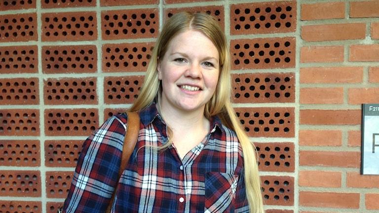 Studenten Emelie Lövgren står framför en tegelvägg