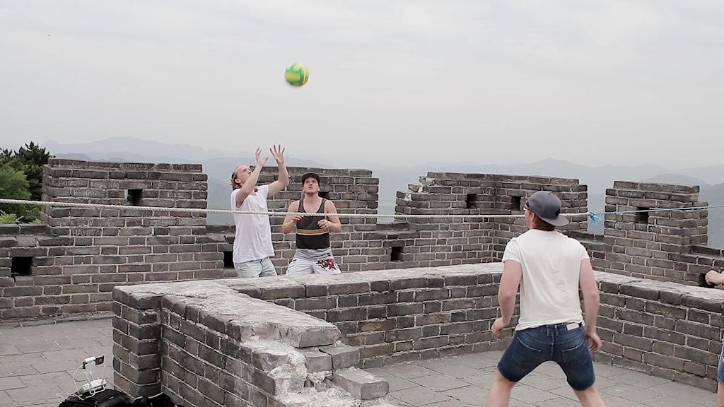Tre unga män spelar volleyboll på Kinesiska muren. Foto: privat