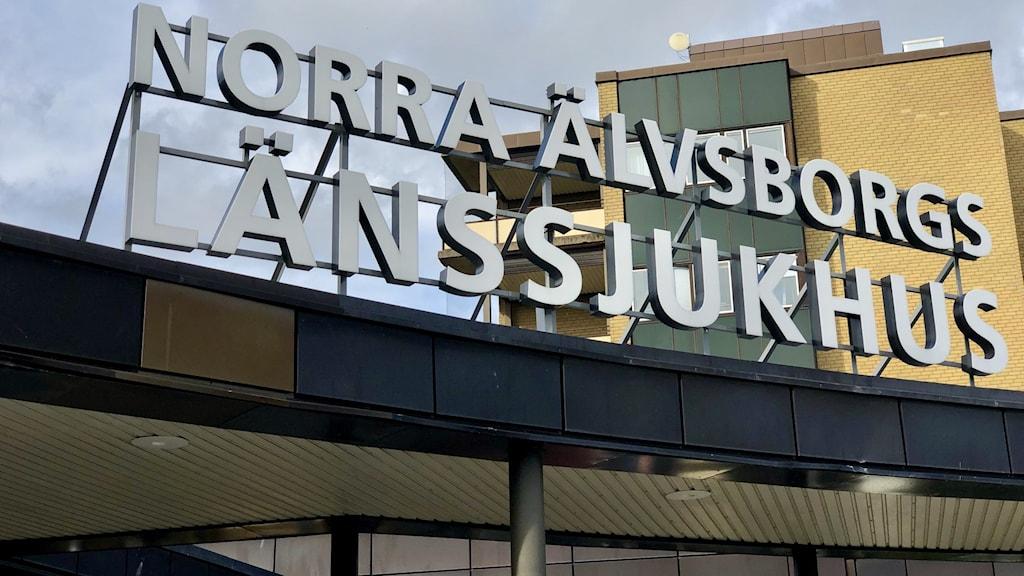 En skylt där det står Norra Älvsborgs Länssjukhus. Huvudentrén till sjukhuset i Trollhättan.