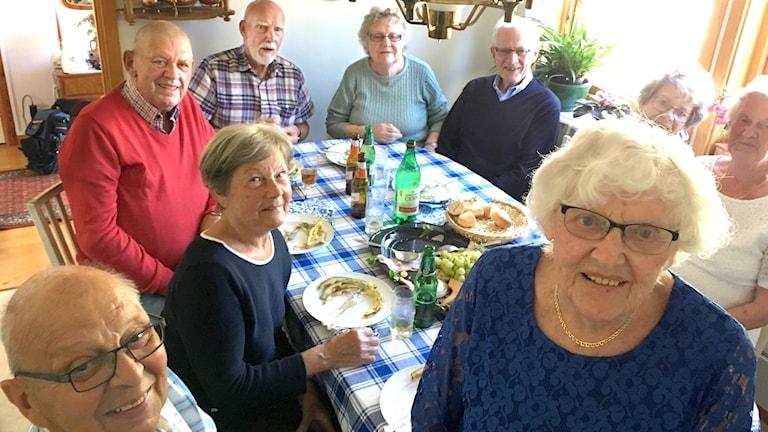 Seniorer runt ett köksbord.