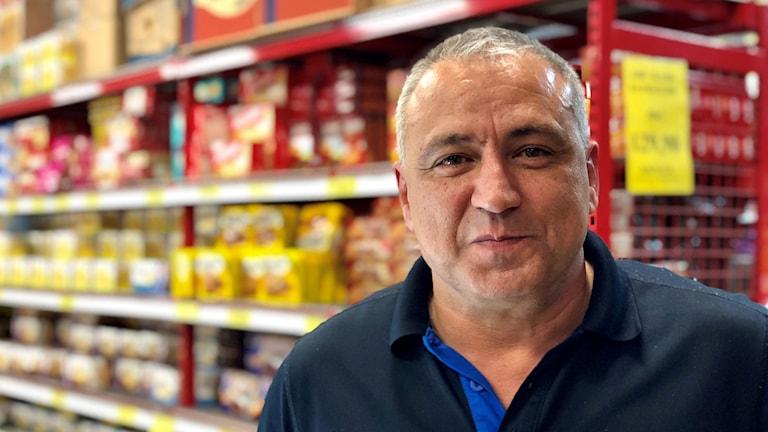 Porträtt av arbetsledare Houssam Nazir där han står mellan hyllorna. Han har mörkblå pikétröja och grått hår.