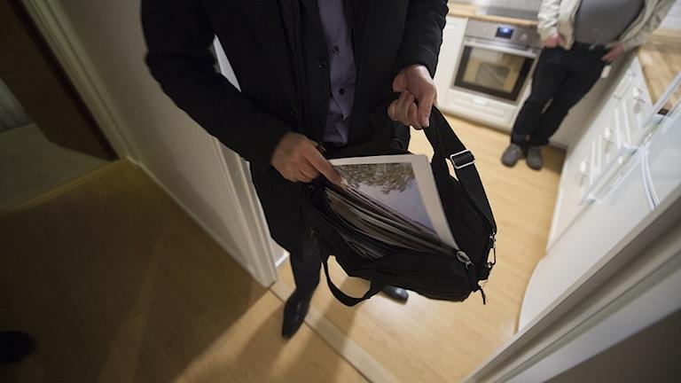 Bild på mäklare som lägger ner broschyr i väska