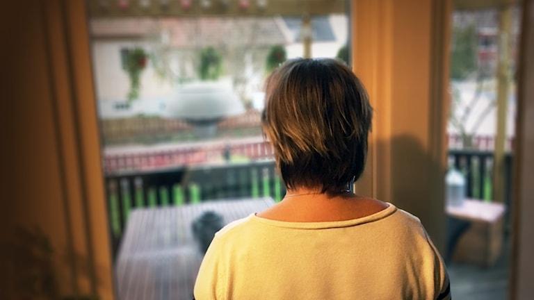 Anonym bild på Marie bakifrån som tittar ut genom ett fönster