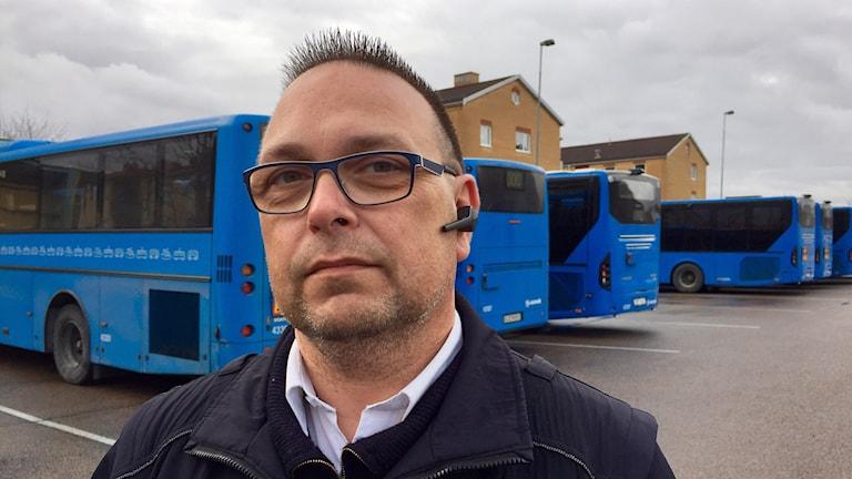 Busschauffören Mikael Romano syns på bild. I bakgrunden syns flera bussar. Han har glasögon på sig, och en bluetooth earpiece. Han ser gravallvarlig ut på bilden. I bakgrunden tecknar sig även en väldigt grå himmel.