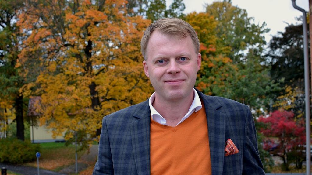 Anders Parment porträttbild med höstiga träd i bakgrunden
