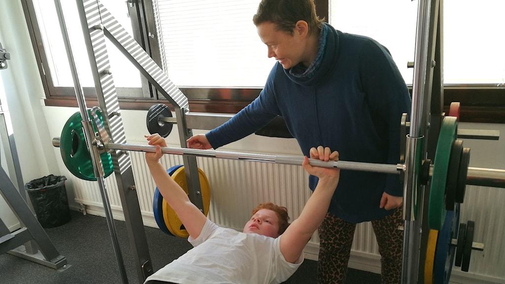 Kvinna instruerar pojke om hur han ska lyfta vikt