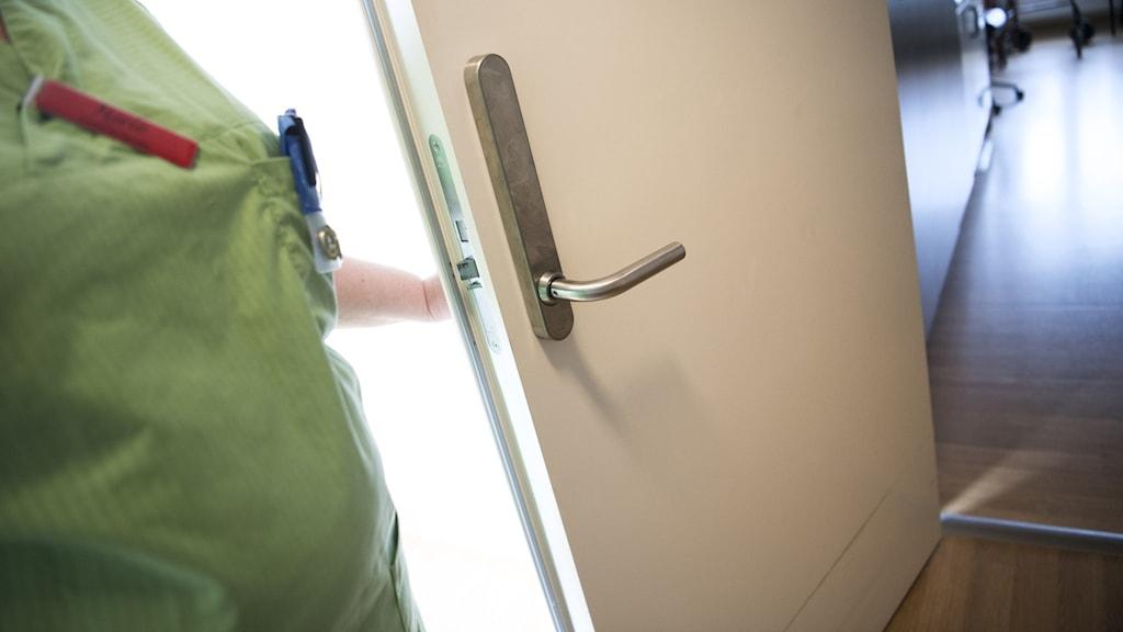 Undersköterska som öppnar dörr till ett rum på äldreboende