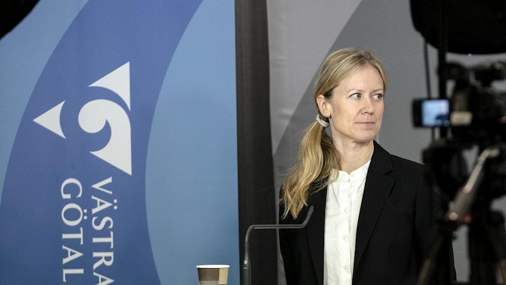Kristine Rygge på en pressträff. VGR-flagga i bakgrunden, kameror i förgrunden.