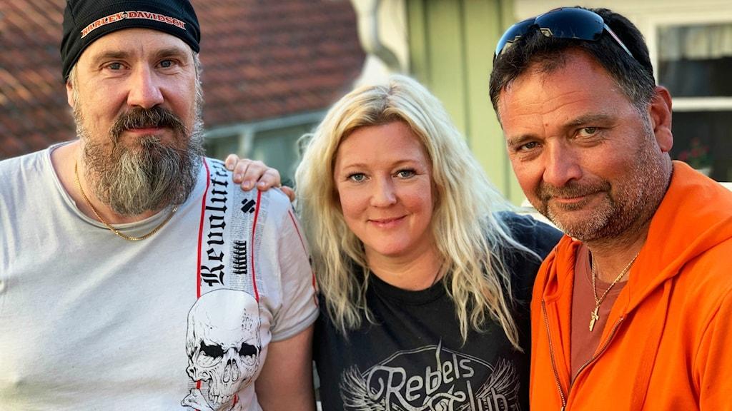 Maria Andersson i mitten med en man på varje sida om henne. De ser glada ut.