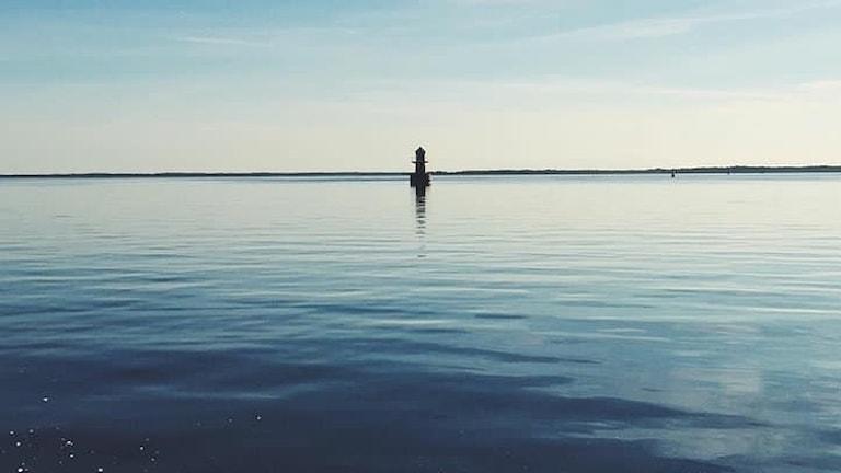 en bild av en fyr i nästan lugnt vatten