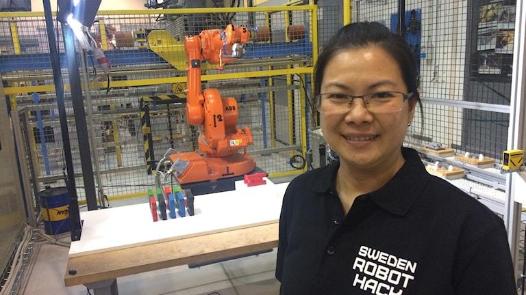 Dong Lu framför en orange robot som staplar träpinnar på varandra.