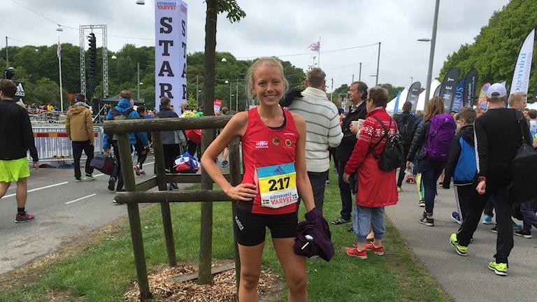 Blond glad tjej i löparkläder, rött linne med nummerlapp på står med handen på höften framför en samling människor