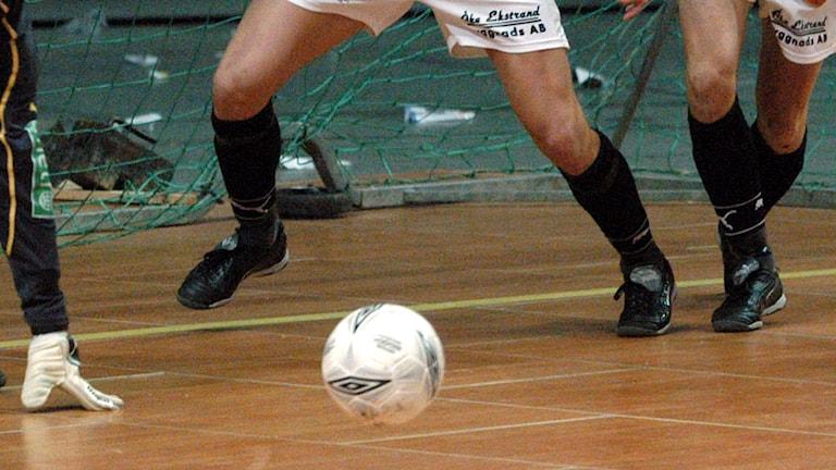 Några fotbollsspelares ben och en fotboll på golvet i en idrottshall.