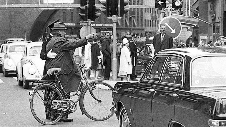 Svart-vit bild på en man som står och pekar förvirrat mot andra sidan gatan, en polis som hjälper till