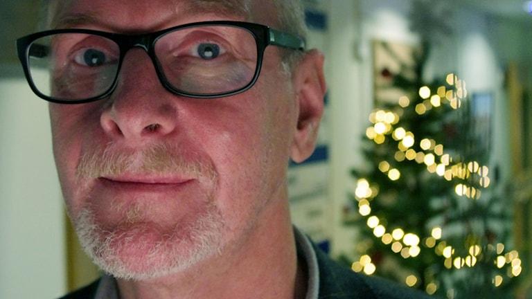 Dals-Eds socialchef Tommy Almström med svartbågade glasögon i närbild i kommunhusets reception. I bakgrunden står en julgran med tänd julgransbelysning.
