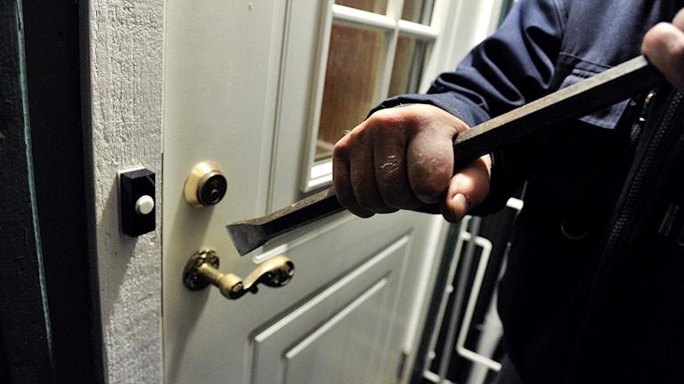 En inbrottstjuv tar sig in i en bostad med hjälp av en kofot.