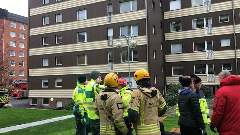 Räddningstjänsten står utanför flerfamiljshuset där det har brunnit.