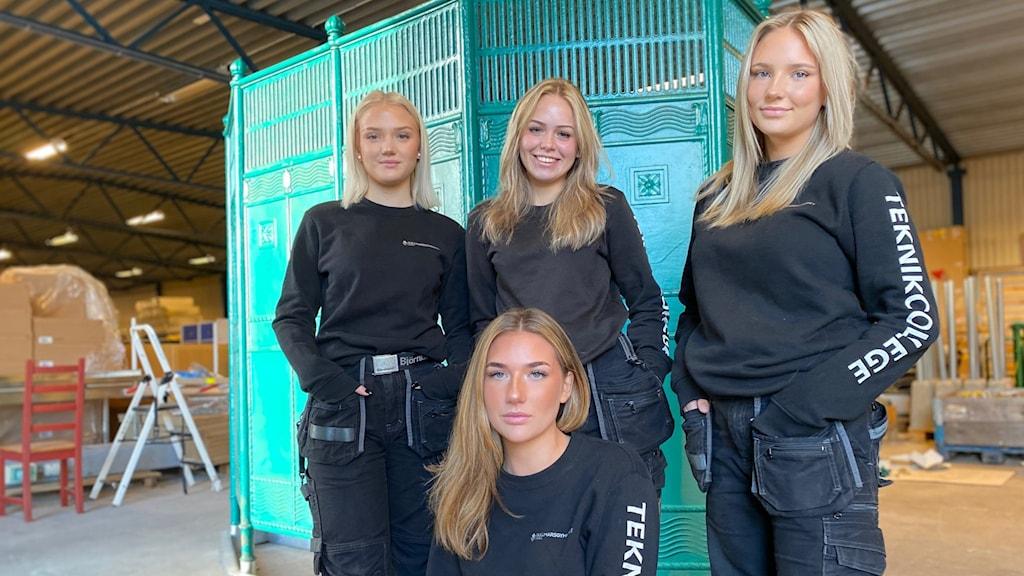 Fyra gymnasietjejer klädda i arbetskläder står bredvid en grön 100 år gammal pissoar