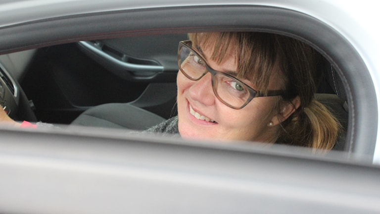 Karolina Almqvist tittar upp ur bilen där hon sitter