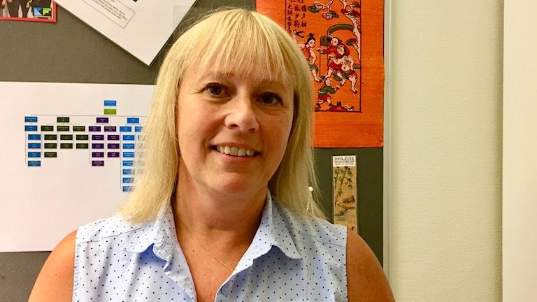 Mariella Niemi på sitt arbetsrum. Hon ler in i kameran och har på sig en blå ärmlös skjorta med svarta prickar.