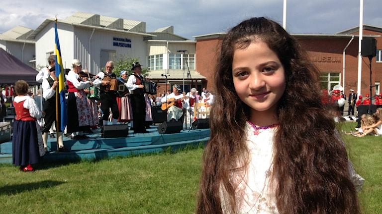 Seleen Ahmed, 11 år, framför scenen i museiparken i Uddevalla. På scenen står en grupp folkmusiker i landskapsdräkter.