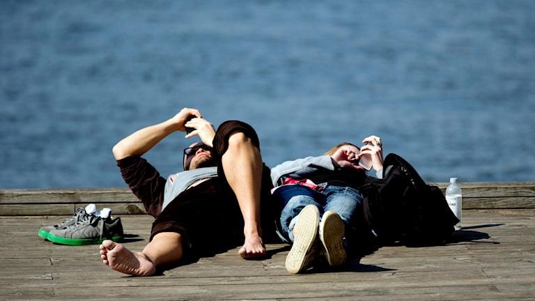Ett par slappar i solskenet på en brygga.