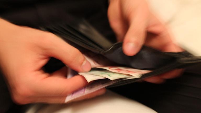 Händer tar ut pengar ur svart plånbok