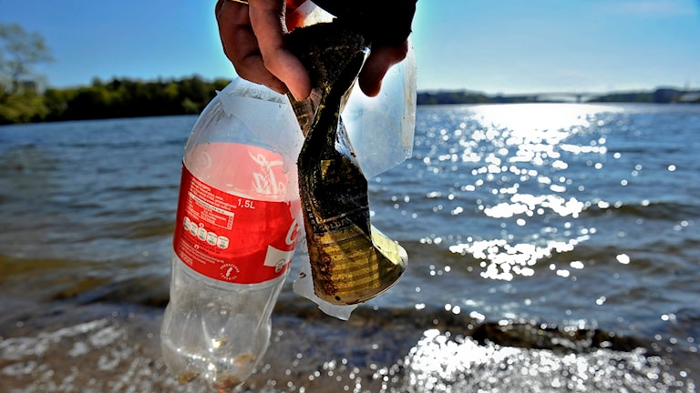 Bild på en PET-flaska, aluminiumburk och plast som hittats vid strandkanten.