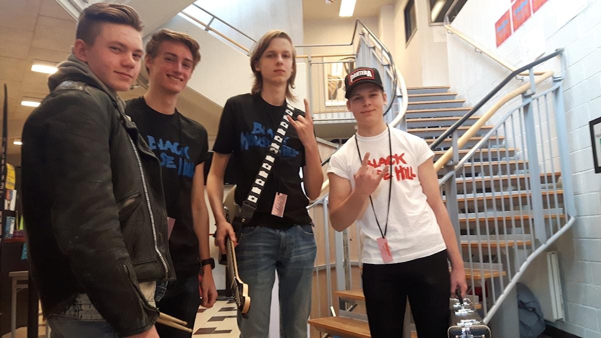 fyra killar står under en trappa och ser glada ut. De har instrument i händerna.