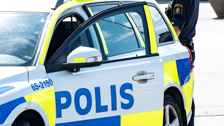 En polis står vid en polisbil