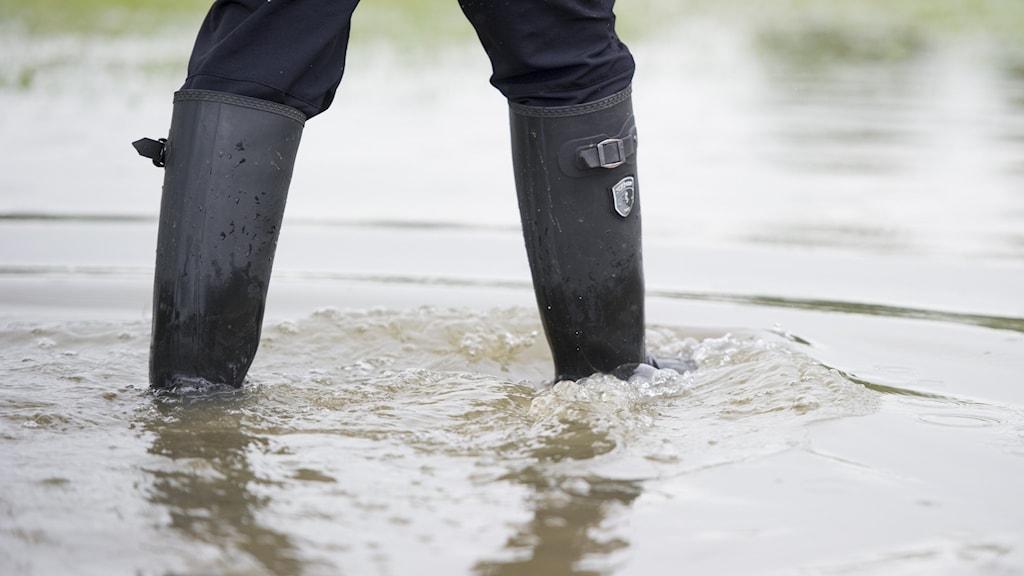 En person i gummistövlar står i högt vatten.