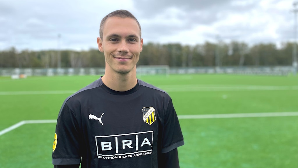 Fotbollsspelaren Tobias Carlsson står framför en fotbollsplan.