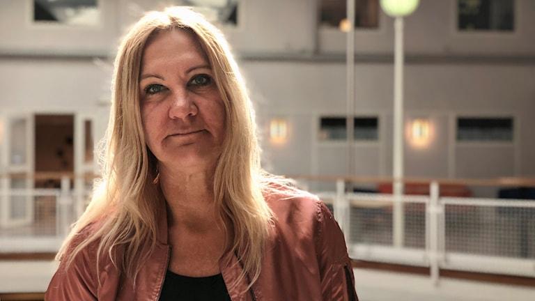 Ulrika Engelbrektsson. Hon är långhårig. Blond. Allvarlig uppsyn. Står i foajen till Högskolecentret. Bär en puderrosa baseboll-jacka.
