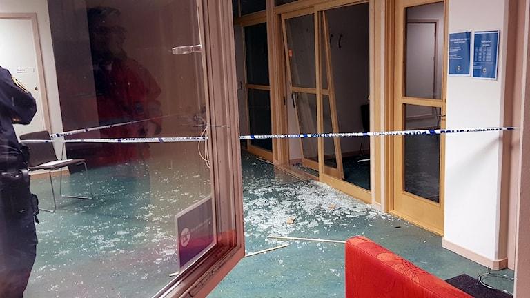 Krossat glas på golvet vid ett kontorsrum.