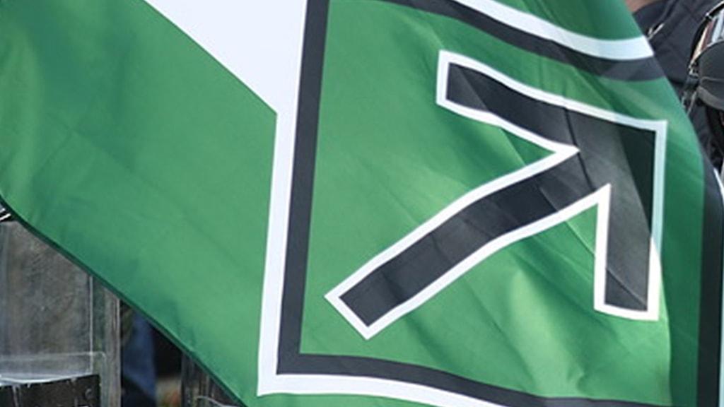 En grön flagga med en svart pil
