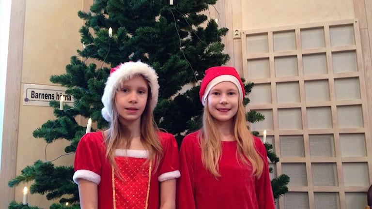 Rebecca Ahlberg och Elsa Wilhelmsson utklädda till tomtar står framför en gran.
