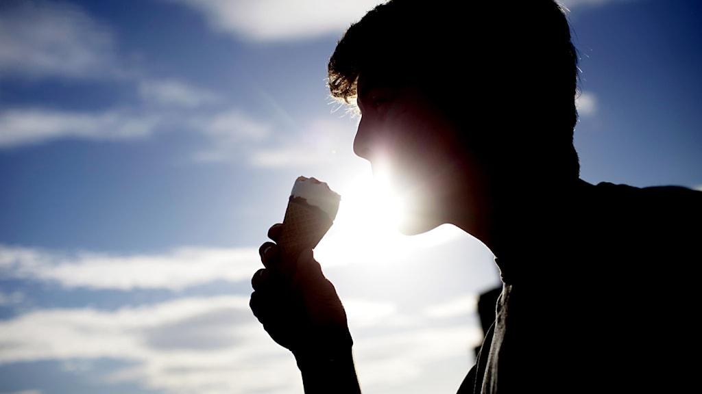 En silhuett på en man som äter glass.