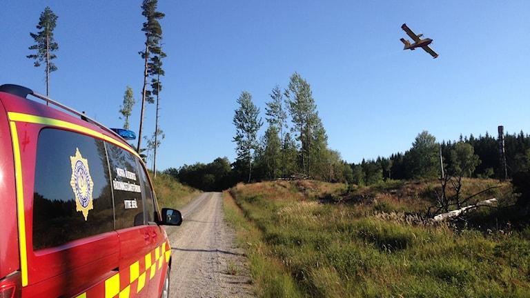 Ett brandflygplan som flyger över skog och ett räddningsfordon på en skogsväg