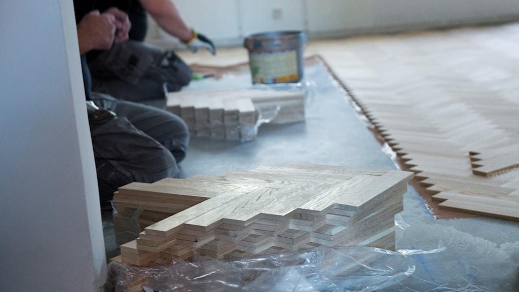 En hantverkare lägger golv.