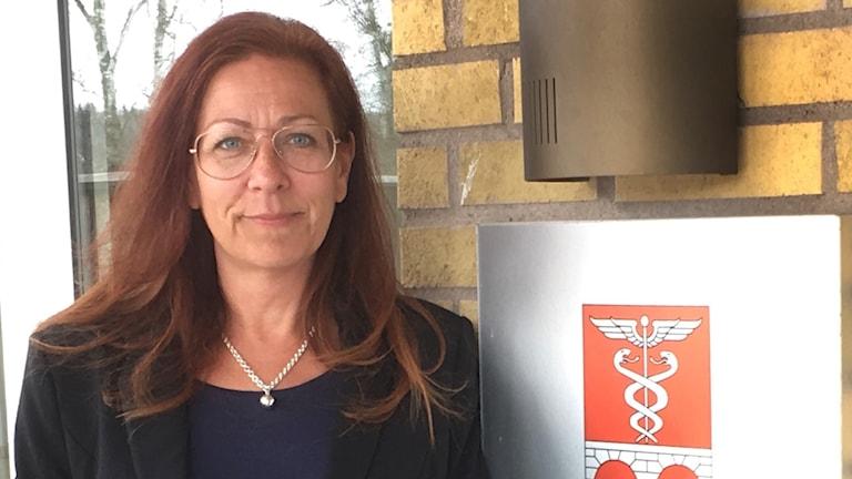 Lena Mossberg, socialchef i Bengtsfors framför en tegelvägg och en skylt med kommunens logga