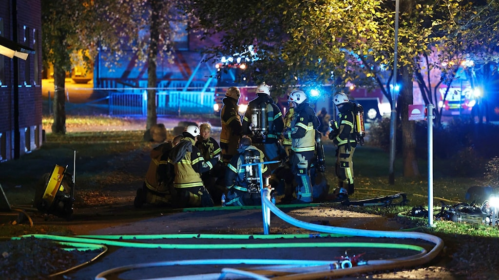 Brandmän samlade i en klunga utanför boendet med slangar i förgrunden.