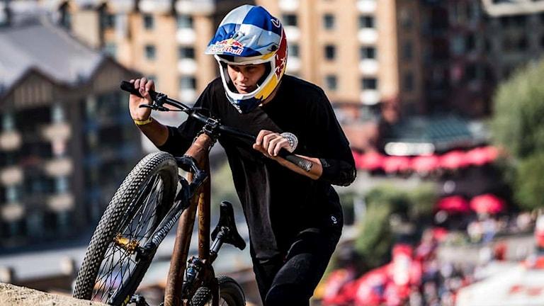 Emil Johansson går med sin mountainbike upp för en backe.