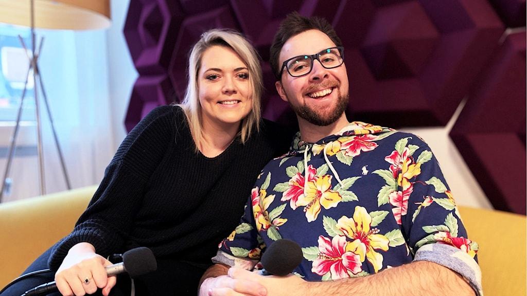 En kvinna och en man sitter i en soffa och ler in i kameran.