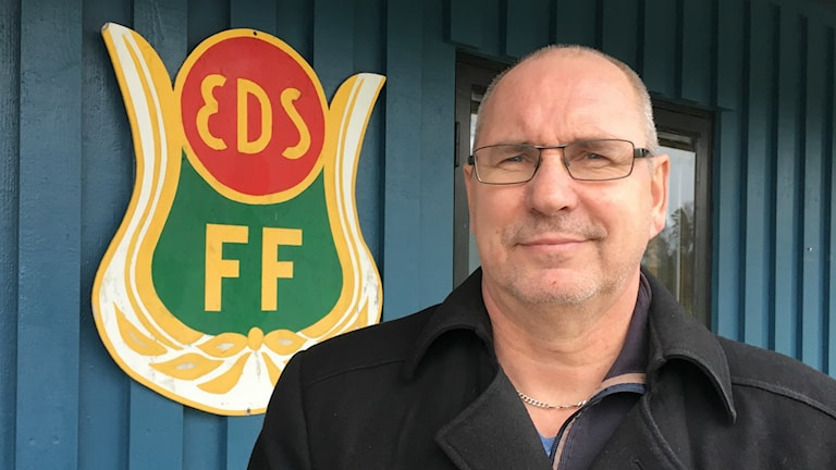 Hans Åkerlundh framför Eds FF:s klubbemblem.