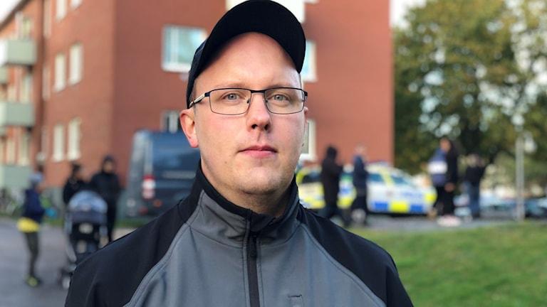 Porträtt av Sami Honkonen. I bakgrunden syns ett lägenhetshus och poliser, polisbilar och förbipasserande.