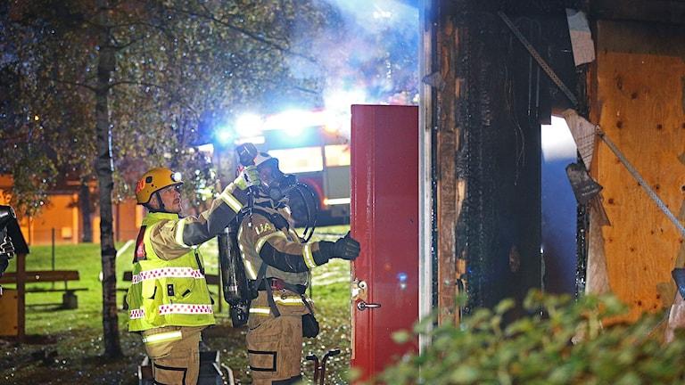 Brandmän står vid en brandskadad förrådsbyggnad vid en förskola i Uddevalla.