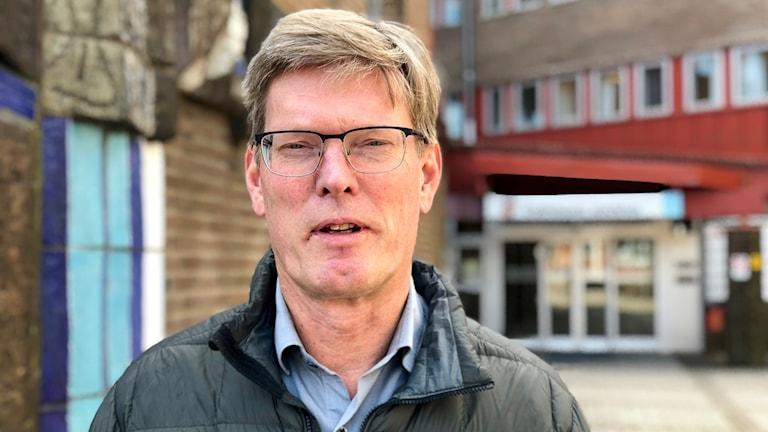 Samhällsbyggnadschefen Håkan Falk. Han är lång och blond. Bär glasögon. Medelålders. Han står utanför entrén till kommunhuset i Trollhättan. Det är ett rätt gräsligt 80-tals hus.